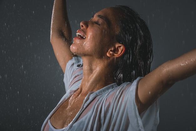 Vrouw voelt zich goed en vrij onder de zomerregen
