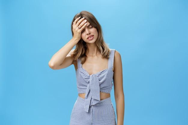 Vrouw voelt zich moe en bezorgd, vol met problemen die facepalm-gebaar maken, voorhoofd stoten met hand sluitende ogen, leunend op handpalm met wanhopige sombere blik, uitgeput staande over blauwe muur