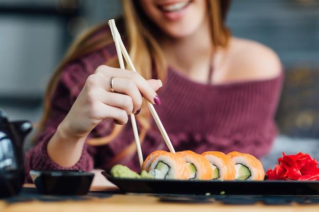Vrouw voelt zich uitgerust en geniet van weekendontbijtsushi