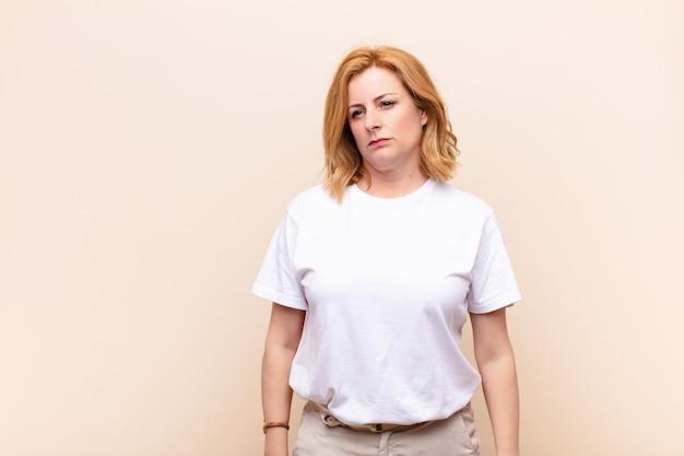 Vrouw voelt zich verdrietig, overstuur of boos en kijkt naar de kant met een negatieve houding, fronsend in onenigheid