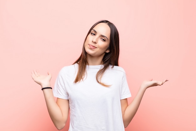 Vrouw voelt zich verward en verward, twijfelt, weegt of kiest verschillende opties met grappige uitdrukking