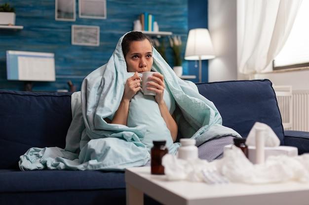 Vrouw voelt zich ziek in een deken met een warm drankje thuis met seizoensgebonden virussymptomen. onwel jonge volwassene met pijn hoofdpijn rustend op de bank met medische behandeling tegen coronavirus