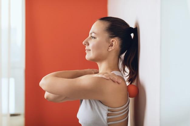 Vrouw voert myofasciale release van hyperflexibele spieren van de rug uit met een massagebal in de buurt van de muur