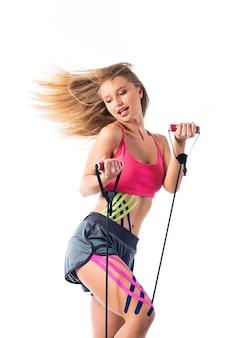 Vrouw voert oefeningen uit met rubber, kinesiotapes die op haar buik zijn geplakt.