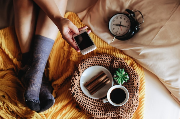 Vrouw voeten op sokken ontspannen op het bed met smartphone en koffie bij het ontbijt