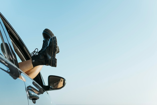 Vrouw voeten uit autoraam in de buurt van zee