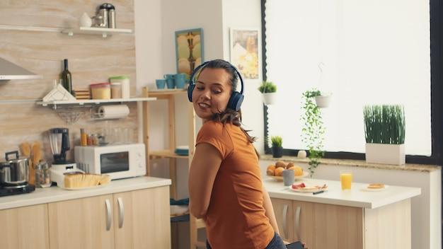 Vrouw vol geluk dansen in de keuken bij het ontbijt. energieke, positieve, vrolijke, grappige en schattige huisvrouw die alleen in huis danst. entertainment en vrije tijd alleen thuis