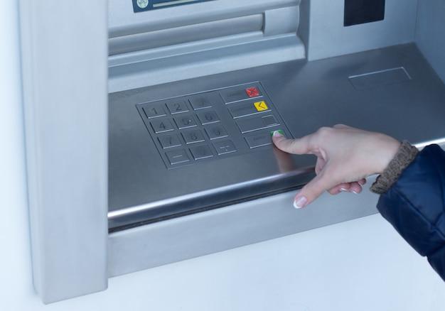Vrouw voltooit een transactie op een geldautomaat buiten een bank terwijl ze geld opneemt voor persoonlijke uitgaven Premium Foto