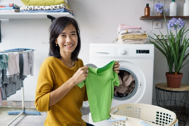 Vrouw voor de wasmachine die naar camera glimlacht terwijl het doen van wat wasgoed binnen kleren laadt Premium Foto