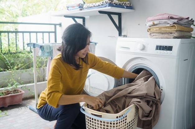 Vrouw voor de wasmachine doet wat wasgoed binnen kleren laden Premium Foto