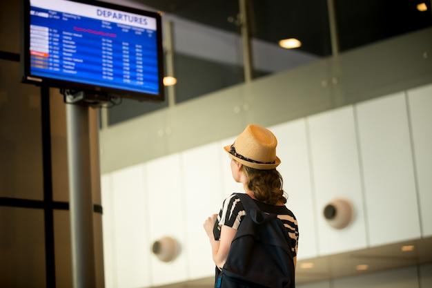 Vrouw voor het vliegveld informatiepaneel