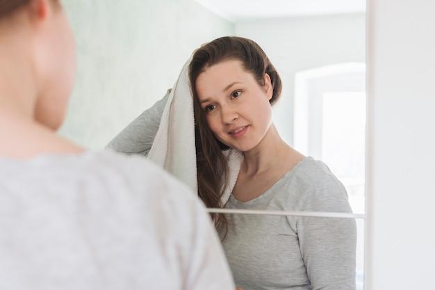 Vrouw voor spiegel in de badkamer