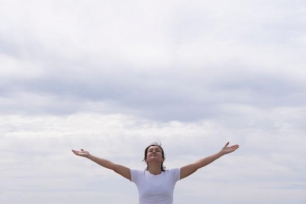 Vrouw vooraan met wit overhemd dat haar wapens opheft aan de hemel