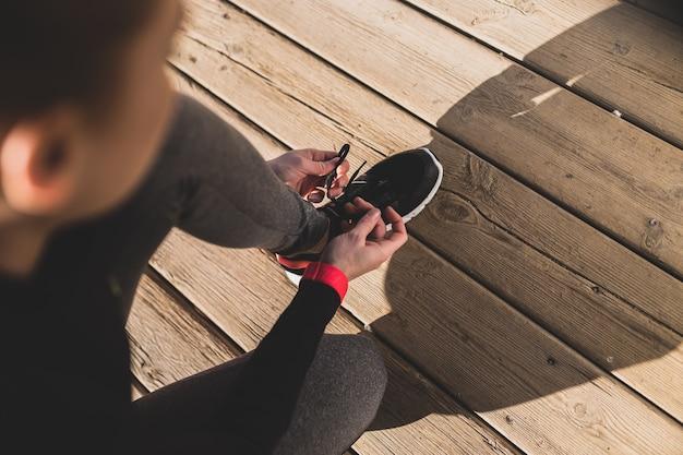 Vrouw voorbereiding van haar gympen voordat u begint te lopen