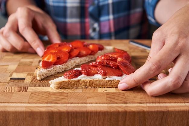 Vrouw voorbereiding van sandwiches met verse bessen