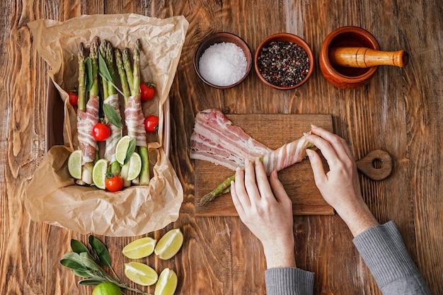 Vrouw voorbereiding van spek verpakte asperges op houten tafel