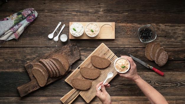 Vrouw voorbereiding van vegetarische spaanse tapas pintxos sandwiches op een houten tafel, bovenaanzicht