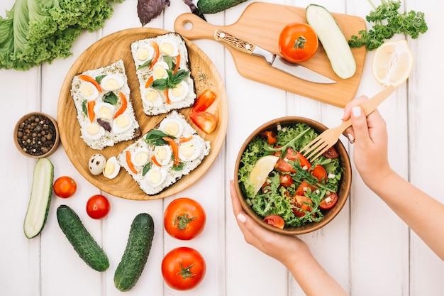 Vrouw vork in salade zetten