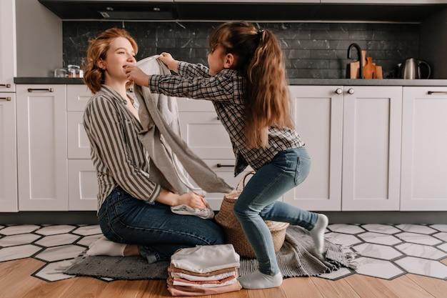 Vrouw vouwt kleren uit wasmand terwijl haar dochter in de keuken speelt.