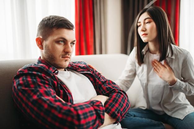 Vrouw vraagt haar man om vergeving na familieruzie. man en vrouw in misbruik, paar in conflict