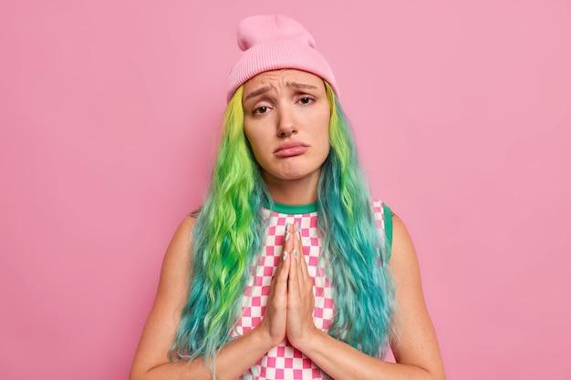 Vrouw vraagt om gunst houdt handpalmen tegen elkaar zegt alsjeblieft maakt plakkerig droevig gezicht laat smeken gebaar heeft geverfd haar gekleed in stijlvolle kleding poseert op roze