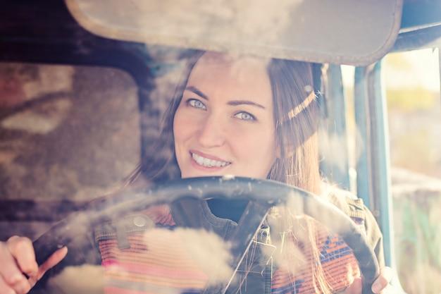 Vrouw vrachtwagenchauffeur in de auto. meisje dat bij camera glimlacht en het stuurwiel houdt.