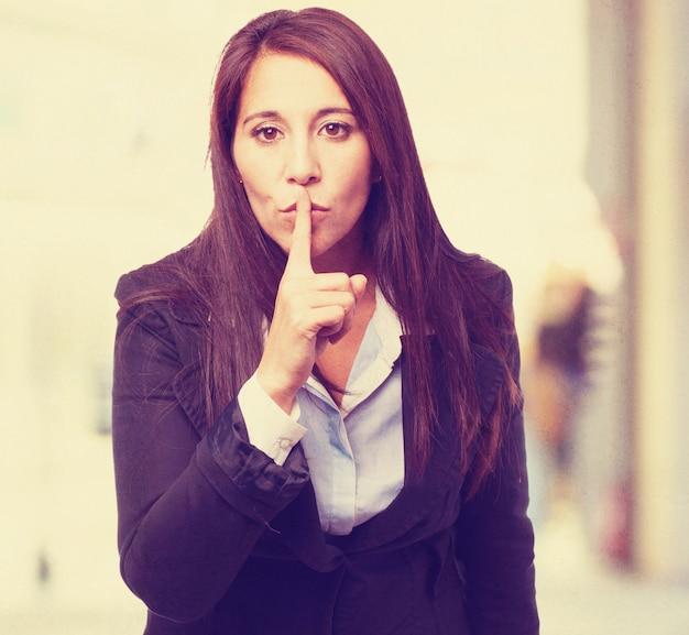Vrouw vragen om stilte met een vinger op haar lippen