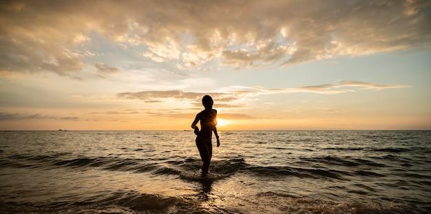 Vrouw vrouw silhouet op het strand bij bewolkte hemel en zonsondergang.