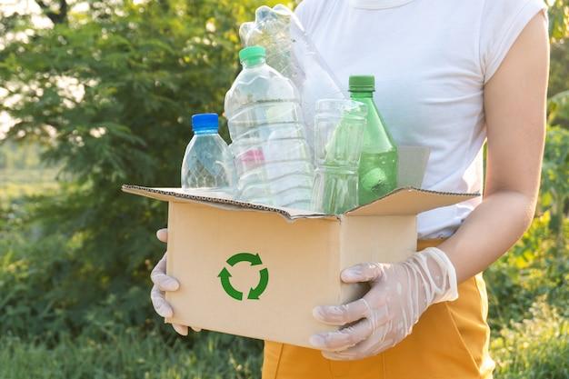 Vrouw vuilnis plastic flessen oppakken in een doos voor recycling concept