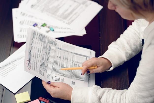 Vrouw vult het belastingformulier in en werkt met belastingdocumenten formulier 1040 aangifteformulier inkomstenbelasting