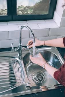Vrouw vult het glas met water uit de stalen kraan in de keuken