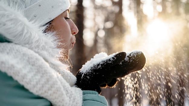 Vrouw waait sneeuw buiten in de winter