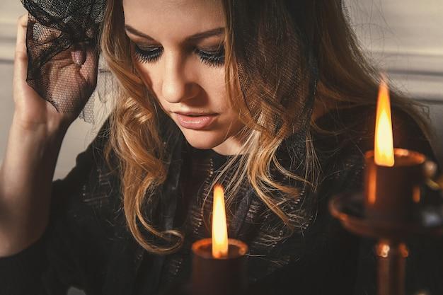Vrouw waarzegger raadt het lot van de nacht aan tafel met kaarsen