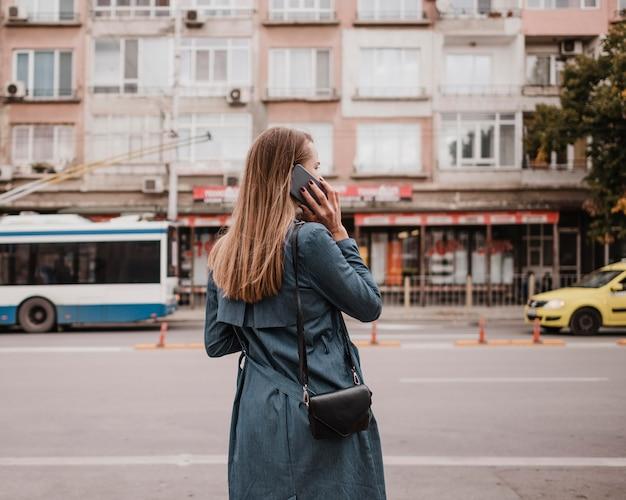 Vrouw wacht op de bus vanaf de achterkant geschoten