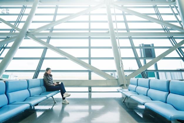 Vrouw wacht op de vlucht, tijd om in te checken op de luchthaven, ruimte te kopiëren.