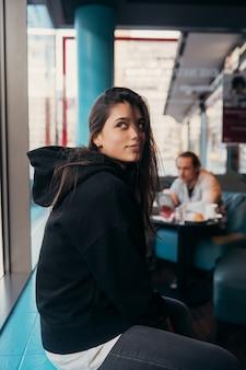 Vrouw wacht op iemand die te laat is, kijkend door het raam
