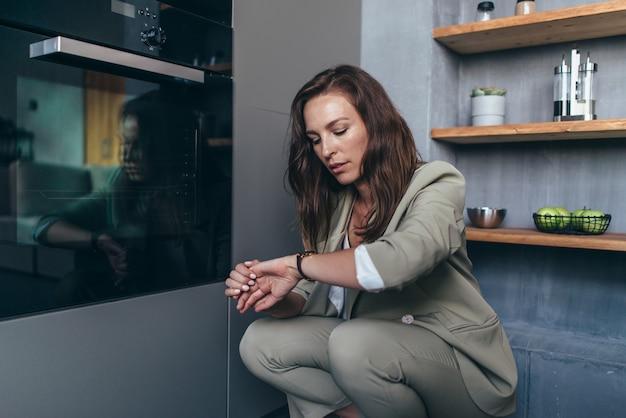 Vrouw wacht op zoek naar de klok voor een maaltijd terwijl ze in de oven zit.
