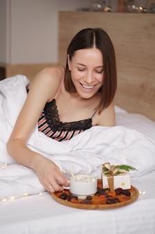 Vrouw wakker op het bed met cadeau en koffie met marshmallows die naast haar staan.