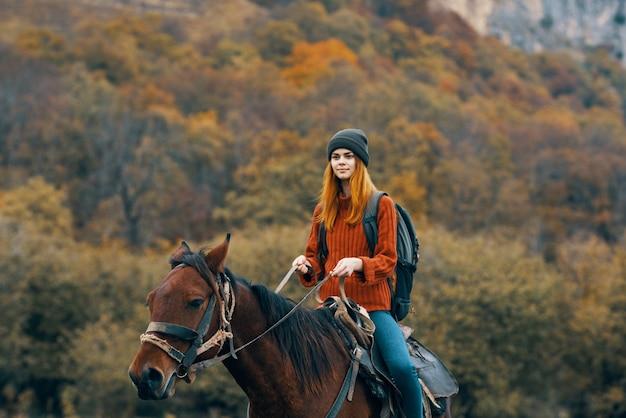 Vrouw wandelaar berijden van een paard in de bergen lopen frisse lucht reizen