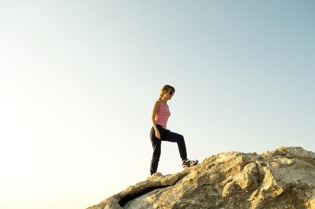 Vrouw wandelaar grote rots klimmen op een zonnige dag