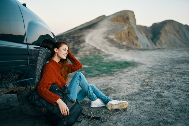 Vrouw wandelaar in de bergen op de natuur zit in de buurt van de auto en de bergen in het landschap van de luchtweg