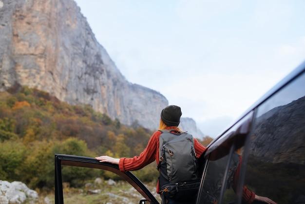 Vrouw wandelaar in de buurt van auto buitenshuis bergen frisse lucht. hoge kwaliteit foto
