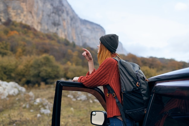 Vrouw wandelaar in de buurt van auto in de avontuurlijke reis van de bergen