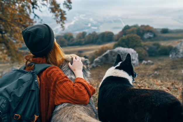 Vrouw wandelaar in de natuur met honden avontuurlijke reizen