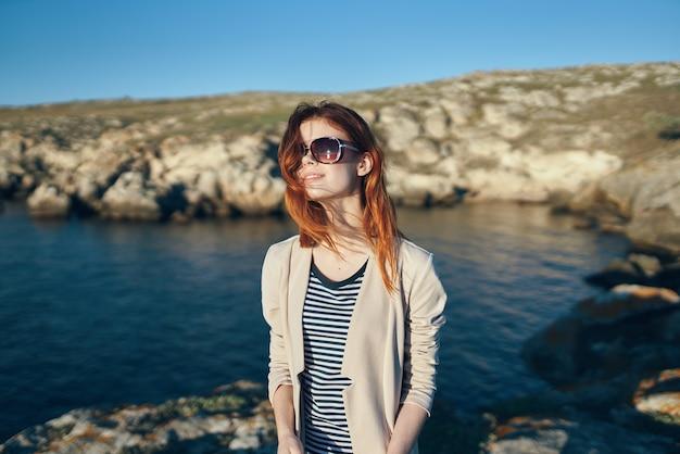 Vrouw wandelaar in t-shirt bril op natuur in de bergen frisse lucht zee levensstijl