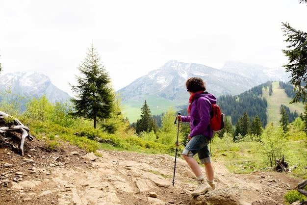 Vrouw wandelaar kijkt naar de top van de berg