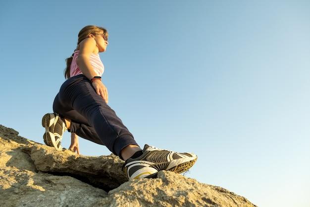 Vrouw wandelaar klimmen steile grote rots op een zonnige dag.