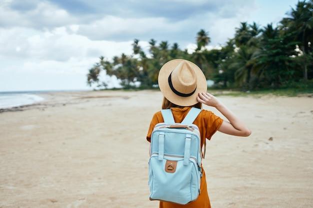 Vrouw wandelaar met blauwe rugzak op het strand