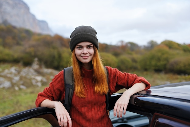 Vrouw wandelaar met rugzak in de buurt van auto op natuur bergtocht