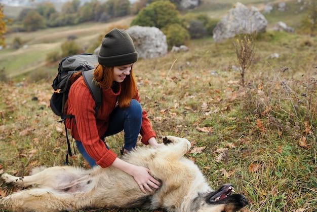Vrouw wandelaar met rugzak in de natuur wordt gespeeld met hondenreisplezier
